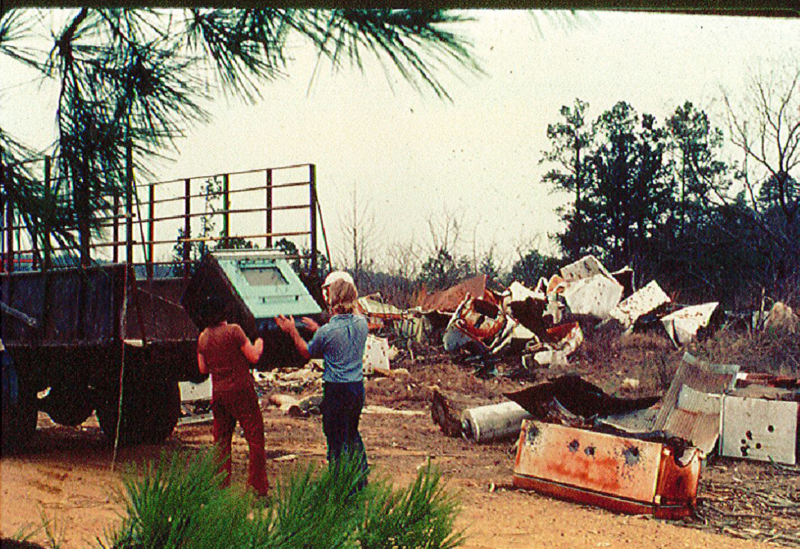 Volunteers loading an old stove into a dump truck.