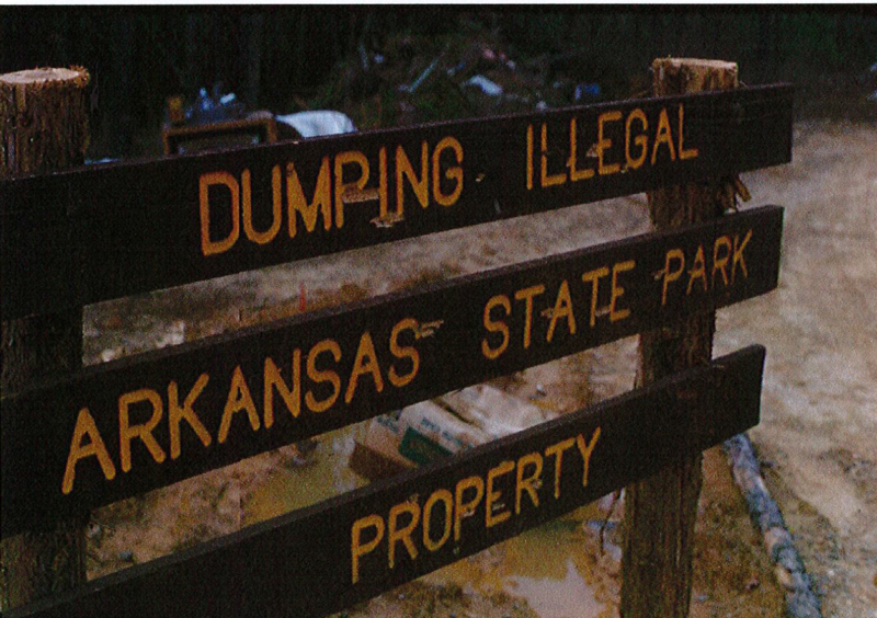 Dumping Illegal sign riddled with bullet holes.