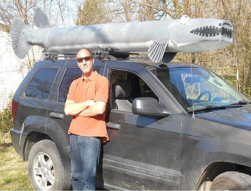 writer Mark Spitzer poses in front of a car he has adorned with a replica gar