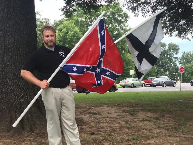 Robert Miller of Arkansas's chapter of the League of the South holds a Confederate battle flag and the LOS flag on Capitol grounds.