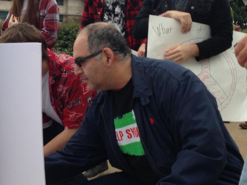 Dr. Tamer Alsebai signing his name to a poster at a rally in support of Syrian refugees at the state Capitol.