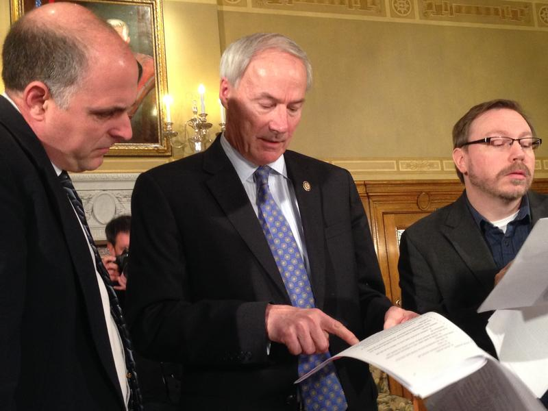 (file photo) Gov. Asa Hutchinson and reporters look at a draft of legislation to make changes to Medicaid.