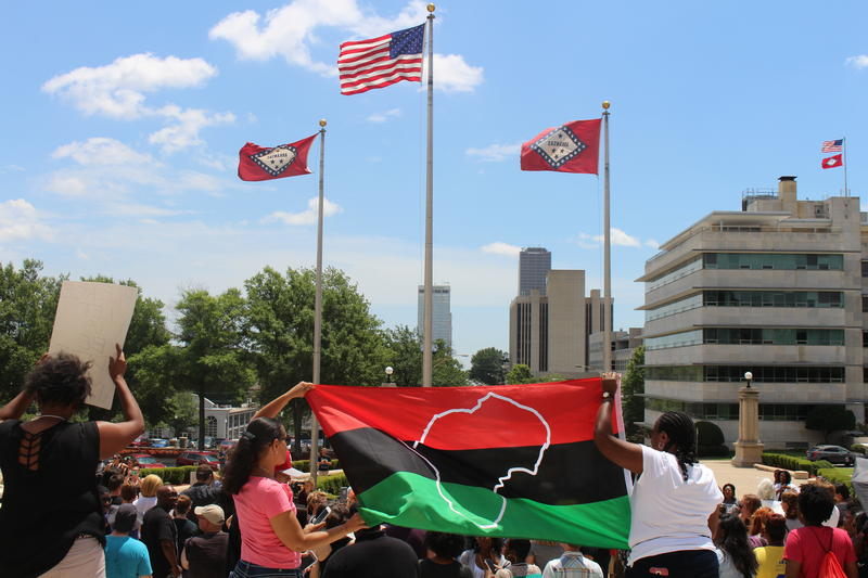 Demonstrators hold a Pan-African or Black Liberation Flag.