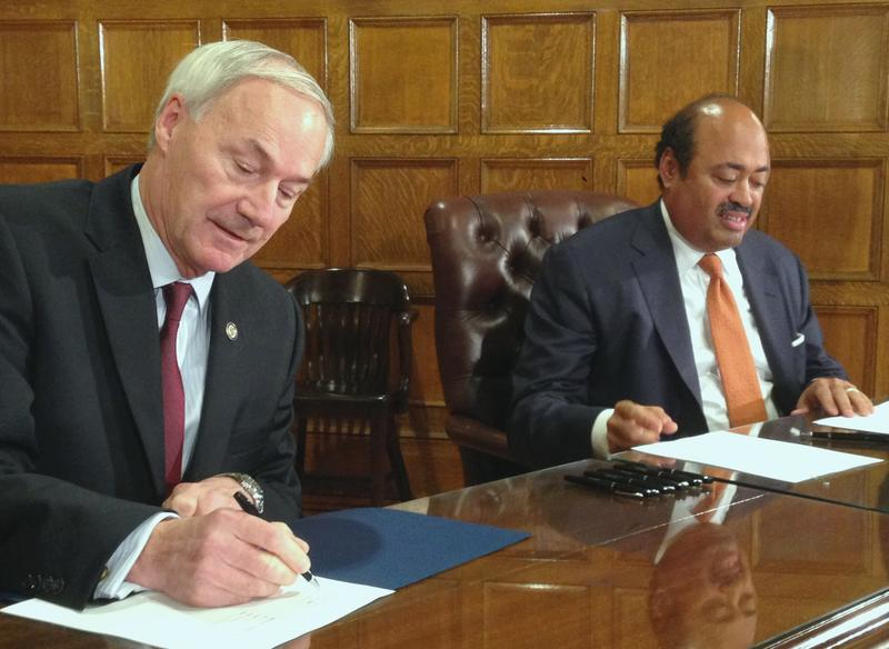 Gov. Asa Hutchinson (R) and Microsoft Vice President of Governmental Affairs Fred Humphries sign a memorandum of understanding (left to right).