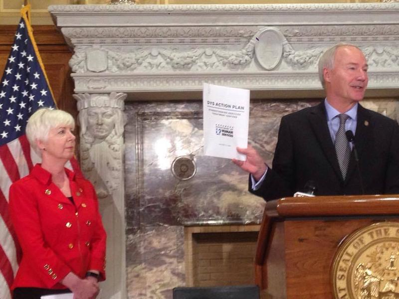 Gov. Asa Hutchinson holds up an action plan from the Department of Human Services. DHS Director Cindy Gillespie stands to the side.