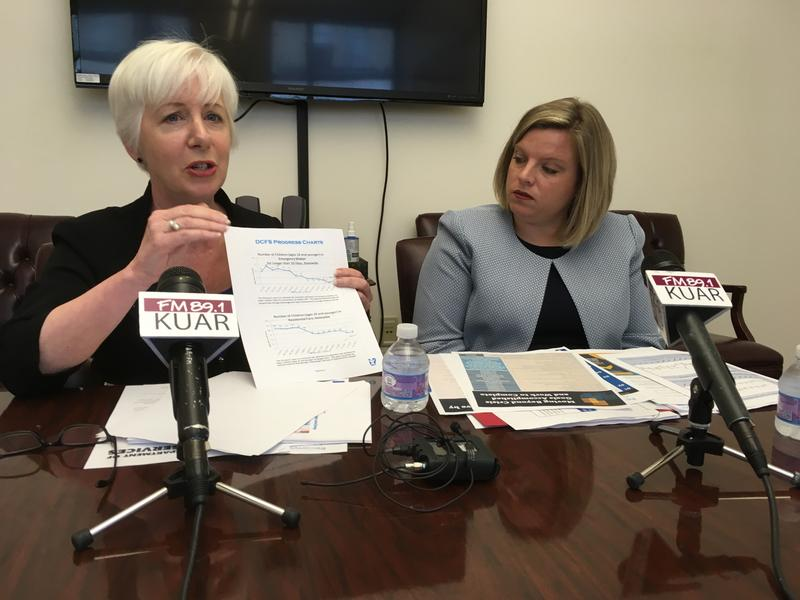 Department of Human Services Director Cindy Gillespie and shows a progress chart to reporters alongside Division of Children and Family Services Director Mischa Martin.