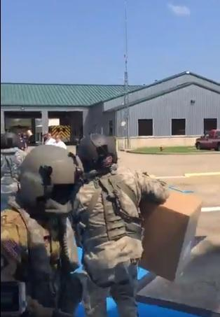 Arkansas National Guardsmen unloading supplies from a helicopter in Texas.