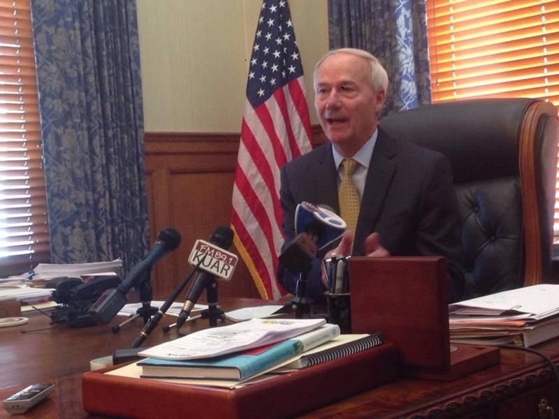 Gov. Asa Hutchinson (R) talking to reporters in his Capitol office.
