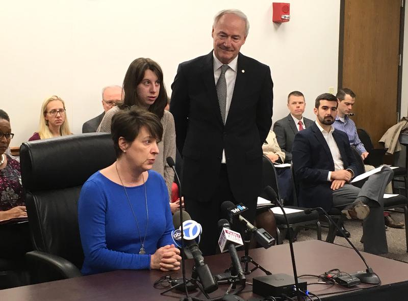 Wendy Reaves (seated) speaks to members of the Arkansas Tobacco Settlement Commission with her daughter Regan and Gov. Asa Hutchinson looking on.
