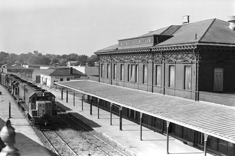 An eastbound Rock Island freight train is seen passing the boarded up Little Rock passenger station in 1976.