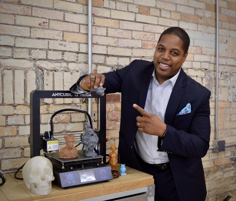Dr. Christopher M. Jones at a 3D printer inside the Arkansas Regional Innovation Hub in North Little Rock.