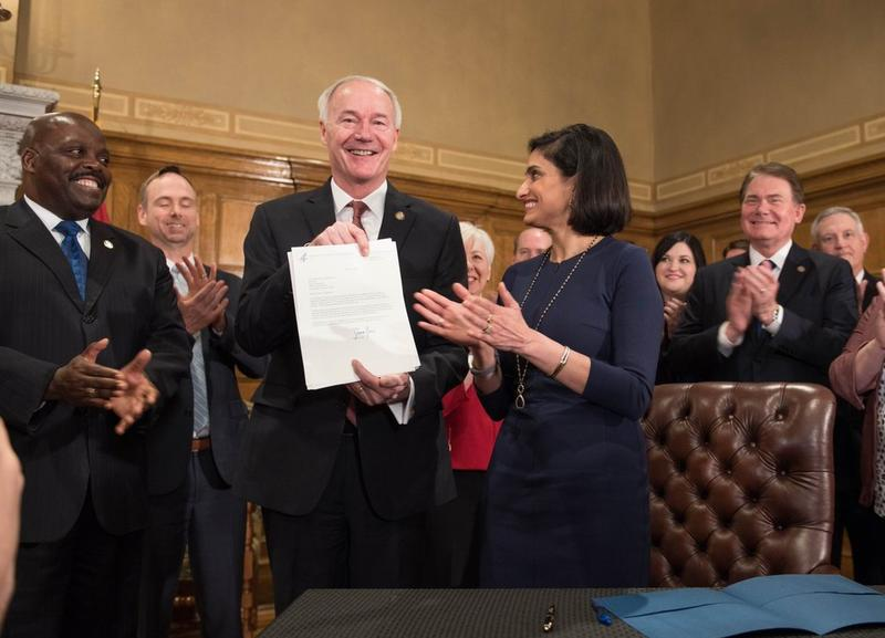 Gov. Asa Hutchinson with Centers for Medicaid and Medicare Services Director Seema Verma holding a signed and approved waiver for Arkansas's Medicaid program on May 30, 2018.
