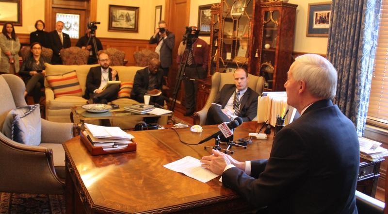 Gov. Asa Hutchinson talking with reporters in his office at the state Capitol.