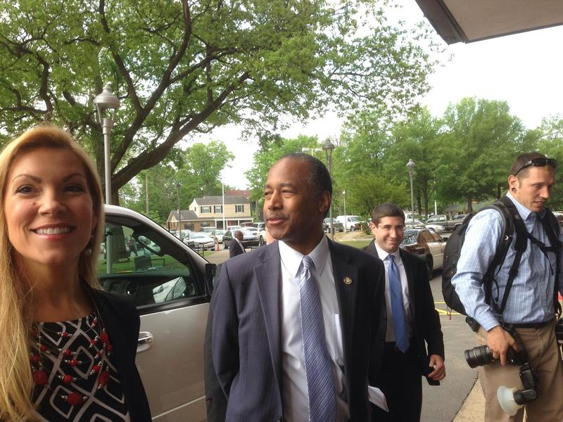 U.S. Department of Housing and Urban Development Secretary Ben Carson looking at demonstrators outside of Parris Tower in Little Rock.