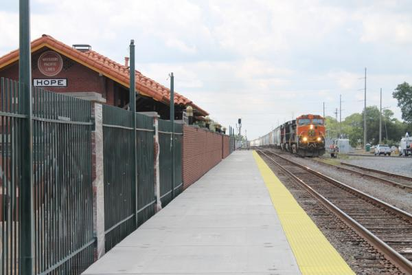 A fright train approaches a newly built platform for passenger service, alongside the old Missouri Pacific train station in Hope in August 2012.