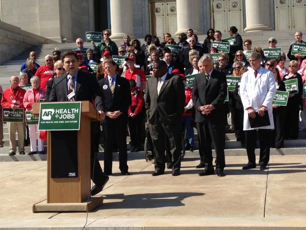 Republican Sen. Jonathan Dismang speaking at the rally on the steps of the state Capitol, with Gov. Mike Beebe and advocates for an expansion.