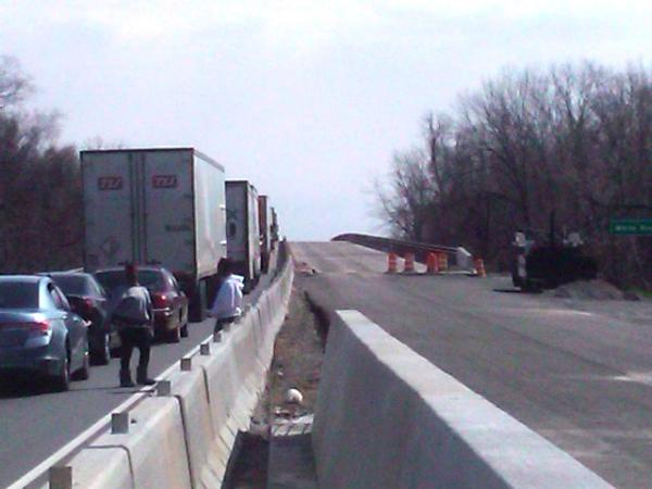 Drivers in stopped traffic near the White River Bridge mill about, waiting for the accident to be cleared.
