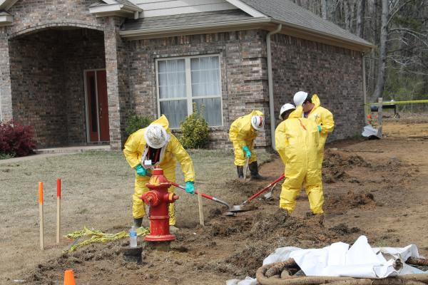 Workers replace contaminated soil from the yard of one of the homes affected by the spill.