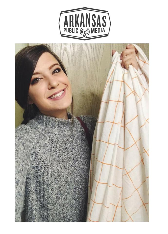 "Sexual assualt victim Gillian Gullett, a sophomore at the University of Arkansas-Fayetteville, holds up a bedsheet she carried around campus in April as part of her social network campaign ""Don't Keep It Under Cover."""