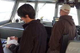 Phil Brown (left) logs data on brine shrimp test while the other aquatics biologist with the GSL Ecosystem, Jim Van Leeuen, uses the GPS system to set up the next test location.