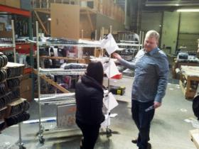 Levelnine COO Mitch Lamb explains shipping system in the 70,000 square foot warehouse space. Shelf has orders ready for packing and shipping. The company currently ships orders throughout the US and Canada plus New Zealand and Australia.