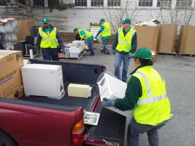 """ERI crews busy unloading hard drives, towers and keyboards from resident's truck to be recycled. Hard drives are rendered unusable by """"punching"""". The process pierces the disc so information from it is unrecoverable."""