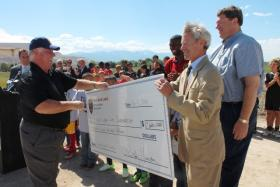 RSL Owner Dell Loy Hansen signs then hands off the symbolic check for the final balance of the total $22.8 million dollars for the 16-field soccer complex. Also pictured:(far left) RSL GM Garth Lagerwey, RSL Defender Kwame Watson-Siriboe, Salt Lake Mayor Ralph Becker and City Councilman Carlton Christensen.