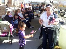 Renee Sorensen of Taylorsville hands out American flags before the program on the City Hall Plaza.