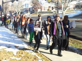 Author and documentary film maker Danny Schechter walks with marchers for Martin Luther King Junior Day. He spoke to the group gathered later of the connection between Nelson Mandela and Dr. King and of his relationship with both men.