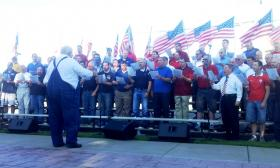 Men's Chorus of Wood Cross under the direction of Rob Ellis. The program included 'I Love Old Glory' by Orrin Hatch and Janice Kapp-Perry. The group also sang 'Amazing Graze.'