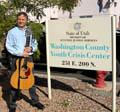 Phillip Bimstein with guitar in front of the Washington County Youth Crisis Center.