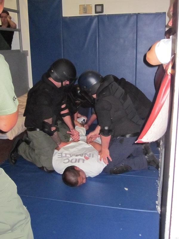 Angelina Cervantes and team subdue an uncooperative inmate in the forced entry training exercise.