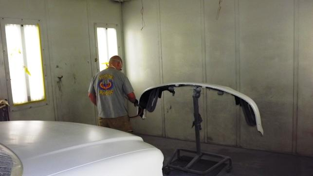 Technician sprays paint on a car in a spray booth designed to limit pollution from car paint