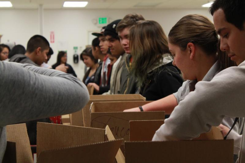 Volunteers place canned food into boxes.