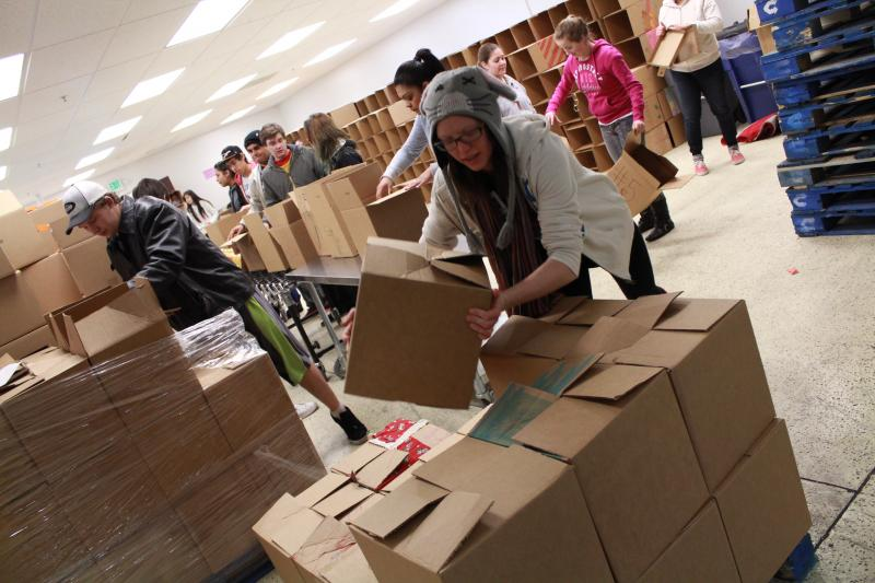 A volunteer places a packed box on a pallet at the Utah Food Bank