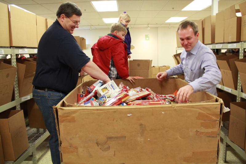 Carlton Christensen and Ben McAdams sort canned food.