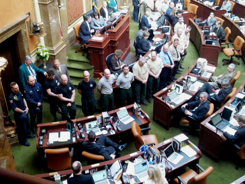 Firefighter Representatives being recognized on the House floor for their work during 2012 wildfire season. Rep. Spencer Cox (R) from Sanpete and Juab Counties seen on lower left recalling Wood Hollow battle.