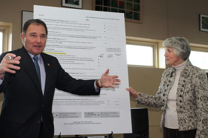 Governor Gary Herbert demonstrates how to donate to the homeless on state tax returns with homeless advocate Pamela Atkinson. (February 8, 2013)