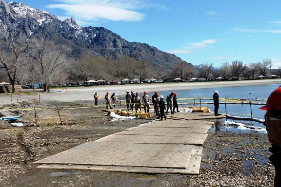 Reporters, officials and Chevron staff view cleanup efforts on the shore of Willard Bay