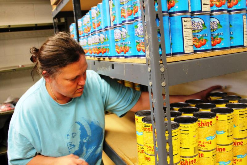 Volunteer Carreen Vigil stocks the shelves at Redwood Neighborhood Center food pantry, which has extended its hours to service people from a closed pantry in Murray.