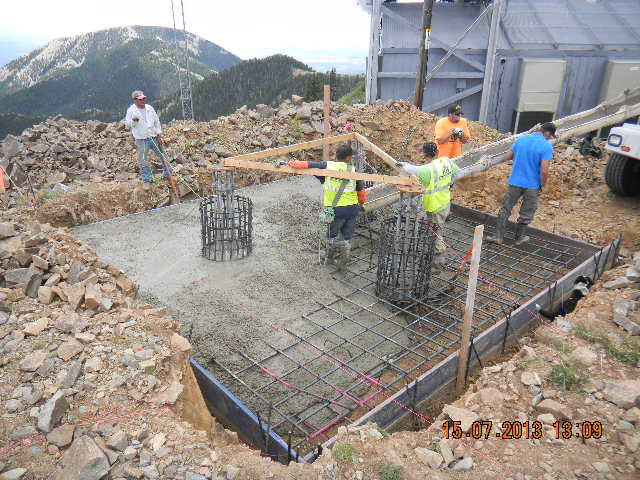 "Crews pour concrete to create the ""pancake"" base of the tower."