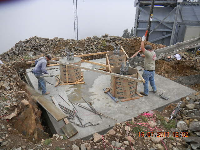 "Crews pour concreate to creat the ""piers"" for the new transmitter tower at Abajo Peak."