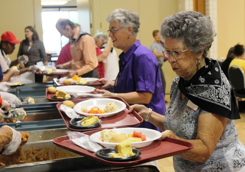 Community members fill their plates at Tenth East Senior Center's 50th birthday celebration.