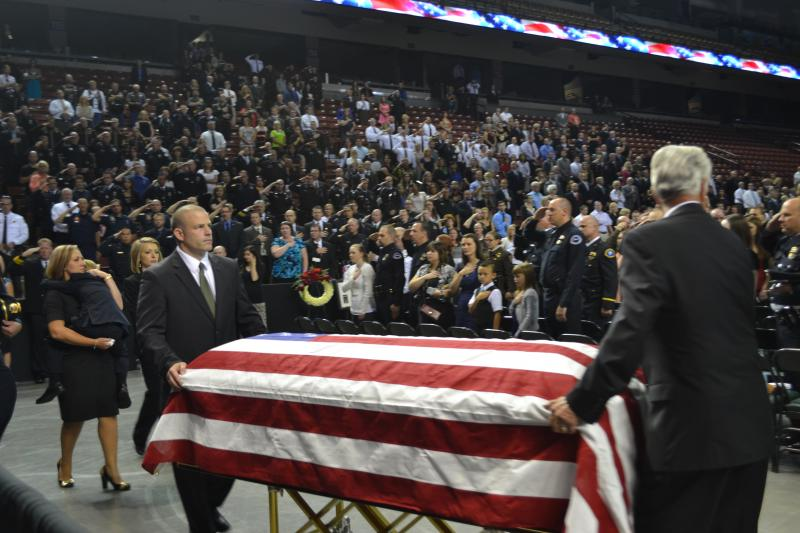 Friends and family members move the casket of slain police officer Derek Johnson into the Maverik Center before the memorial service.
