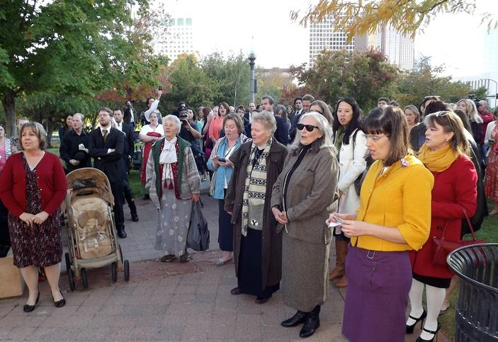 Members and supporters of Ordain Women sing a hymn before trying to gain entrance to the priesthood session of the LDS general conference.