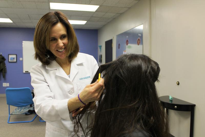 Hair Maidens co-owner Ashley Hafer demonstrates a combing technique for lice treatment.