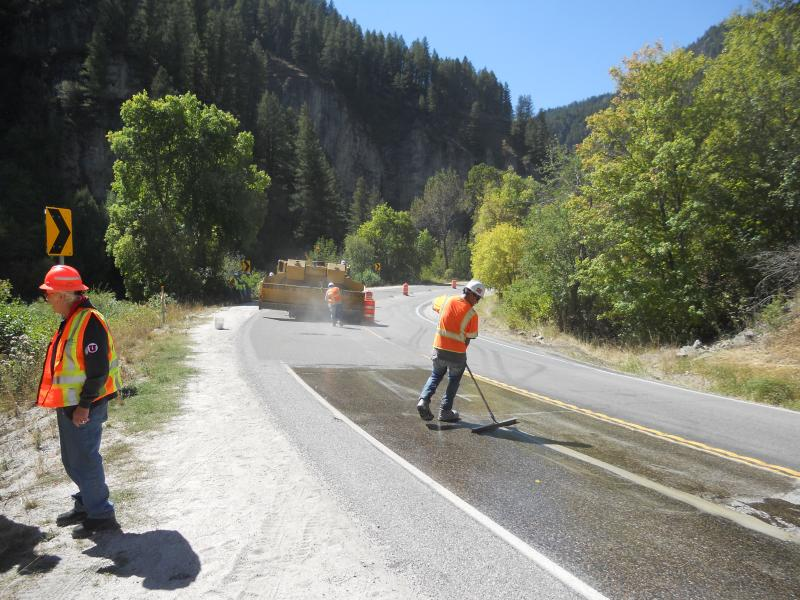 UDOT crews work on applying a high-friction surface treatment to a high-risk curve of highway in Logan Canyon.