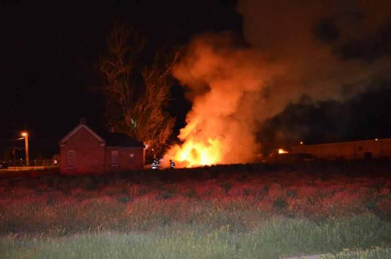 A fire burns near an abandoned building in south Provo early in the morning of April 22