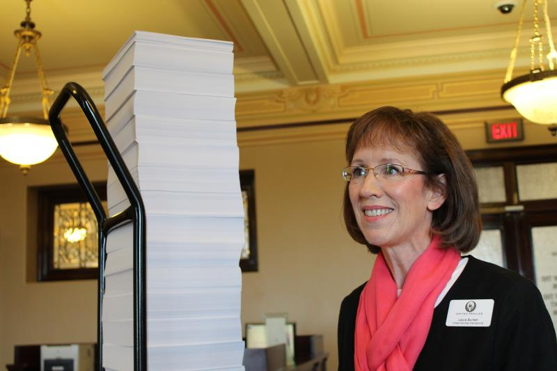 Laura Bunker, president of United Families International standing next to a stack of petitions.