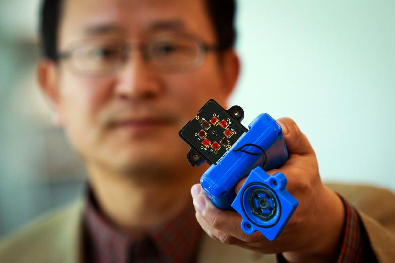 Ling Zang, a University of Utah professor of materials science and engineering, holds a prototype detector that uses a new type of carbon nanotube material for use in handheld scanners to detect explosives, toxic chemicals and illegal drugs.